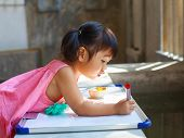 image of writing  - lovely kid practice for writing on white broad before class learning in pre kindergarten - JPG