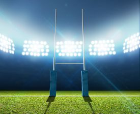 stock photo of lamp post  - A rugby stadium with rugby posts on a marked green grass pitch at night under illuminated floodlights - JPG