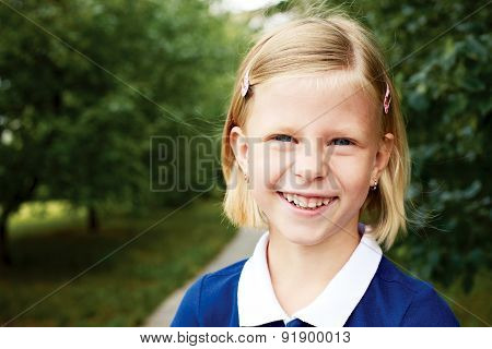 Portrait Of A Smiling Schoolgirl In A Blue Dress