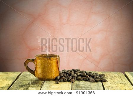 Coffee Cup And Coffee Beans On Wooden Table With Grunge Background