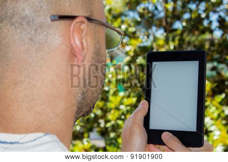 Man Reads An E-book In A Garden