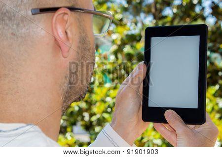 Man Reads An E-book In A Garden