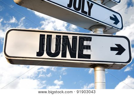 June direction sign with sky background