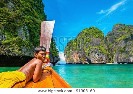Thai boy on colorfull longtail boat in Thailand