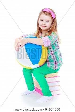 Little girl sitting on a stack of books and holding an inflatabl