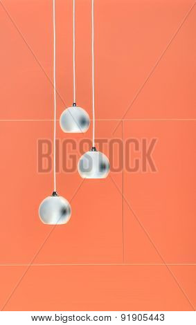 Orange negative collage of three ceiling lights, loft-style inte