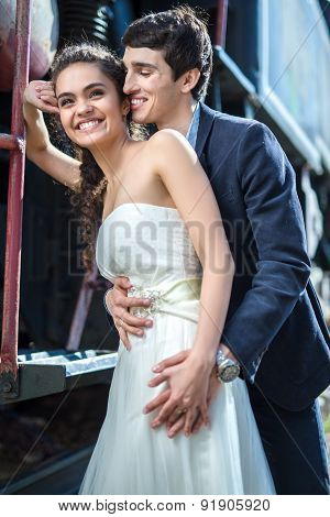 Portrait of happy wedding couple near the old steam locomotive