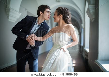 Happy couple playfully goes down a long corridor
