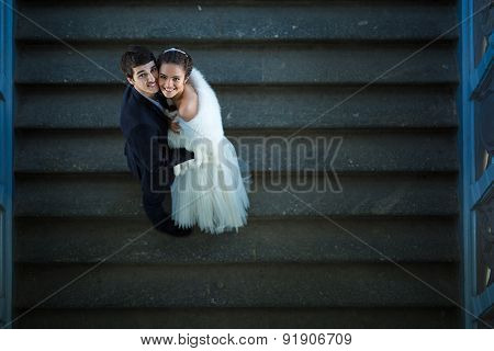 Couple in love is embracing on the stairs and looks up