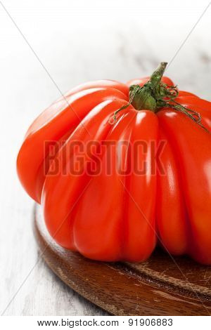 Fresh tomato on old wooden board.