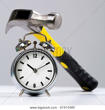 Conceptual Hammer Tool On A Round Alarm Clock