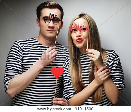 people, party, love and leisure concept - lovely couple holding party glasses and hat on sticks, over gray background