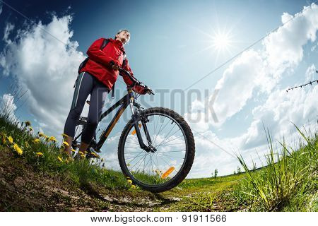Young lady standing with bicycle on a green meadow at sunny day