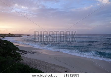 Waves Break And Crash Towards The Hanakailio Beach With Dramatic Blue-pink Cloudy Skyline At Dusk
