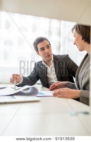 Two Young Business People Discussing At The Table