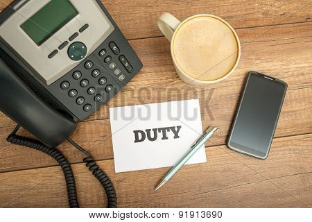 White Card With Duty Text On Top Of Worktable