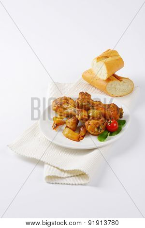 freshly roasted chicken legs and vegetables on white plate