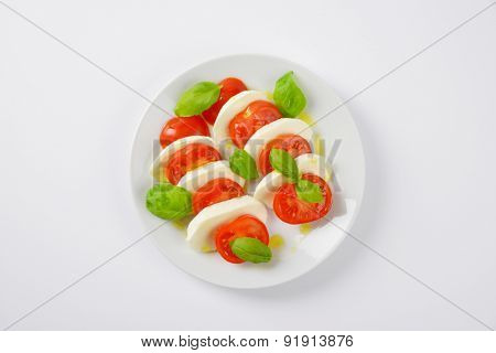 plate of fresh caprese salad on white background