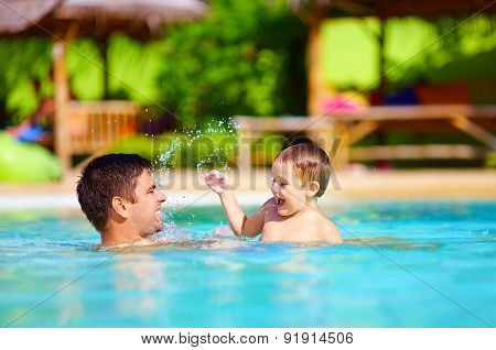 Joyful Father And Son Having Fun In Pool, Summer Holidays