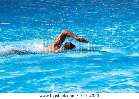 young man swim crawl style in outdoor swimming pool, sunny summer day