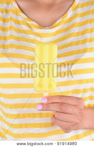 Closeup of a woman holding a lemon ice pop in front of her torso. The woman is wearing a yellow and white striped shirt and has pink nail polish.