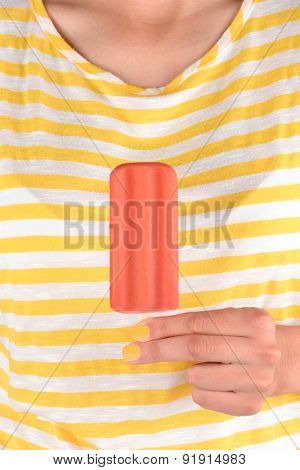 Closeup of a woman holding a red ice pop in front of her torso. The woman is wearing a yellow and white striped shirt and has yellow nail polish.