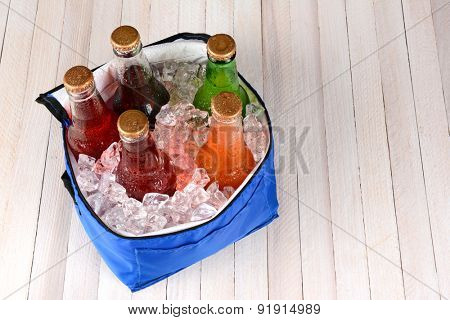 High angle shot of a collapsible cooler filled with crushed ice and soda bottles on a rustic wood picnic table. Horizontal format with copy space.