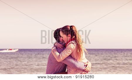 Couple Sitting On Beach Relaxing And Hugging