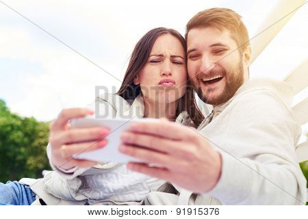 outdoor photo of funny couple sitting and taking a selfie on smartphone