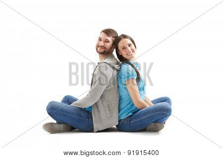 young couple in love sitting back to back on the floor and looking at camera. isolated on white background