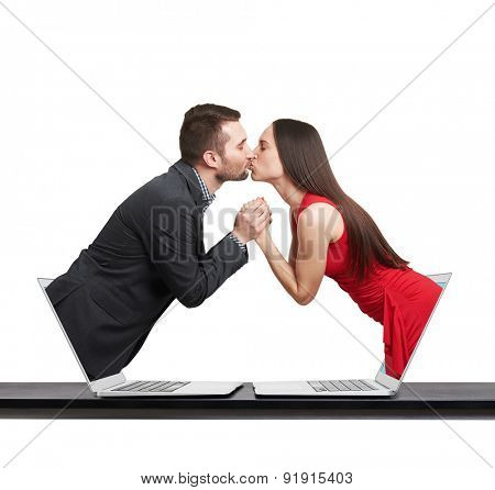 young man got out of the computer and kissing beautiful young woman who got out of another computer over white background