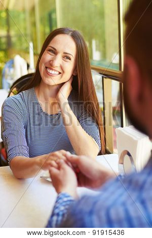 happy loving couple on date at the restaurant. young smiley woman looking at man and holding hand