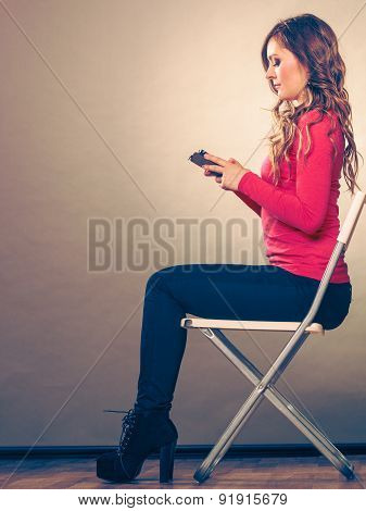 Woman Using Mobile Phone Sitting In Chair.