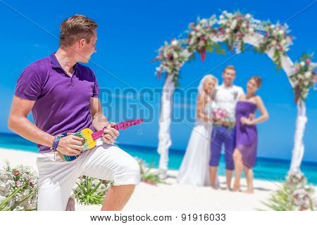 bride, groom and guests enjoying beach wedding in tropics, on wedding arch, setup background