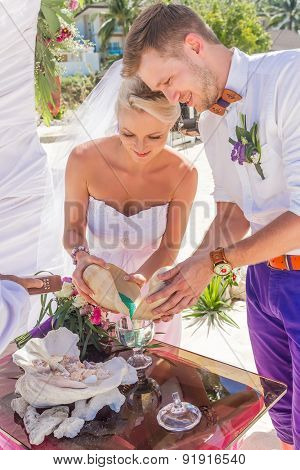 young loving couple, bride and groom, on their wedding day on wedding setup, arch, venue background, sand ceremony
