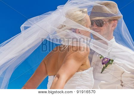 bride and groom enjoying beach wedding in tropics, on wedding arch, setup background