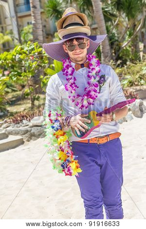 young happy groom having fun on wedding day with lots of hats and flowers in tropics