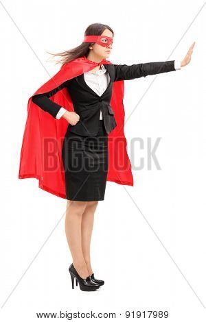 Full length portrait of a female superhero making a stop sign with her hand isolated on white background