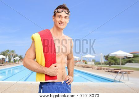 Young man with swimming goggles carrying a towel over his shoulder and posing in front of a swimming pool