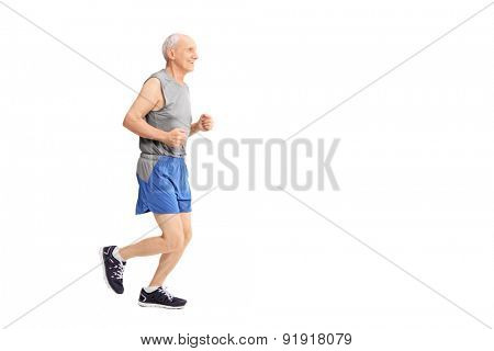 Profile studio shot of a cheerful senior jogging in sportswear isolated on white background
