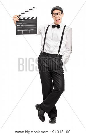 Full length portrait of a young movie director holding a movie clapperboard and leaning against a wall isolated on white background