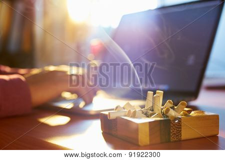 Man Using Laptop And Smoking Cigarette In The Morning