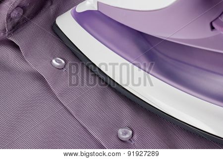 Smoothing-iron On Purple Shirt With Selective Focus