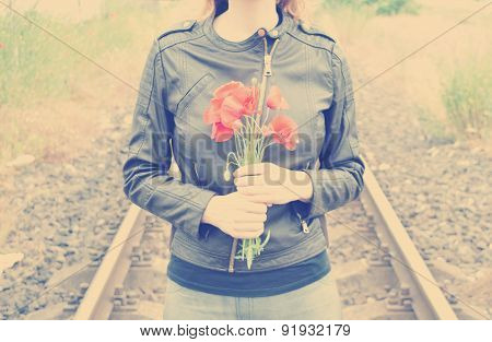 Young woman with poppies in her hands