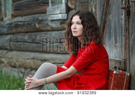 Young Woman Sitting On Threshold Of Old Log Cabin With Retro Suitcase