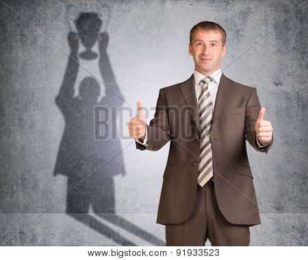 Businessman with shadow holding winner cup