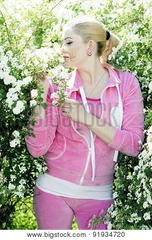 the beautiful girl in a pink suit in the blossoming bush