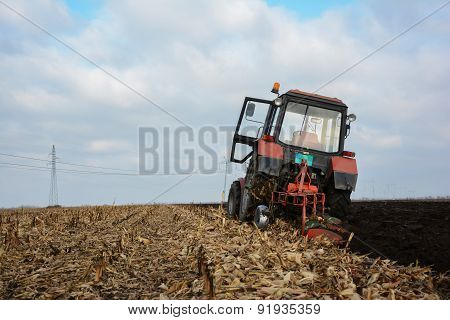 Tractor In The Field In The Middle Of Tillage