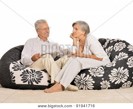 Happy elderly couple resting at home