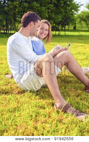 Portrait Of Happy Smiling Caucasian Couple Sitting Together On The Grass Outdoors And Listening To M
